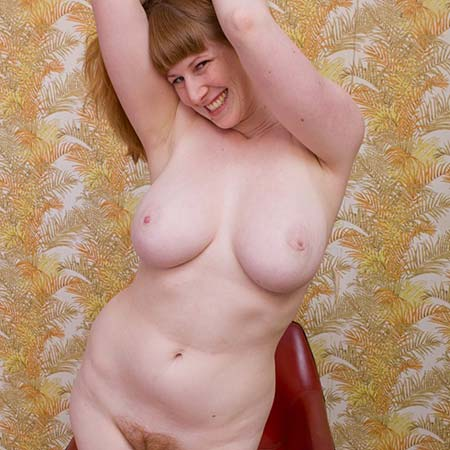 Pale busty redhead Chloe B. has fun stripping