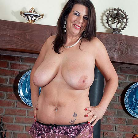 Mature Lulu Lush strips by the fireplace